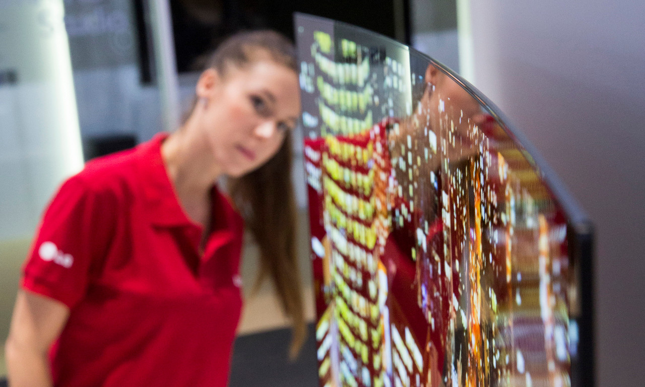 An employee of LG Electronics looks behind a curved organic light-emitting diode, oled, television screen at IFA, one of the world's largest trade fairs for consumer electronics and electrical home appliances, in Berlin, Germany, Thursday, Sept. 5, 2013. The screen is just 4.3mm, 0.17 inches, thin and weighs just 17 kilograms, 37.48 pounds, IFA will take place on the Berlin Exhibition Grounds from Sept 6 to 11, 2013. (AP Photo/Gero Breloer)