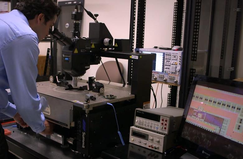 Чип под микроскопом. Его увеличенное изображение выводится на экран справа (фото: stanford.edu).