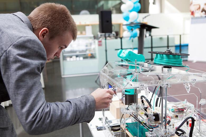 Олег Зобов демонстрирует модель промышленного робота и создавший её 3D-принтер.