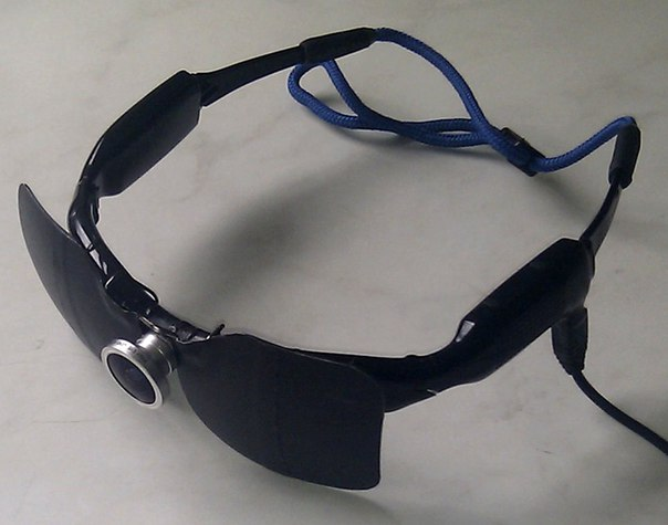 """Комплект системы """"vOICe""""  состит из видеоочков с wifi передатчиком и мини-компьютером спряженные по радиоканалу."""