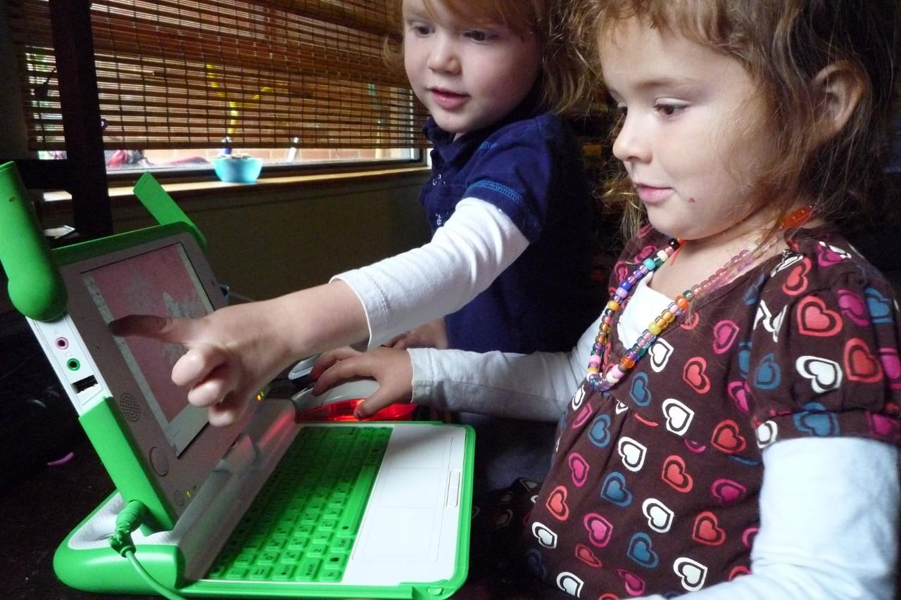 Презентабельных фотографий своего ноутбука у меня пока не получилось, а в Сети его снимков давно нет. Поэтому иллюстрируют сегодняшнюю колонку просто случайные кадры так или иначе связанные со старой цифровой техникой. Здесь, к примеру, дети играют с нашумевшей в своё время портативной персоналкой OLPC образца середины нулевых. Она старая и медленная, но для ребёнка она интересней «настоящих компьютеров», потому что может ему принадлежать.